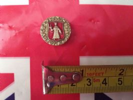 ROUND RUSSIAN BADGE WITH OLD FIGURE ON RED BACKGROUND